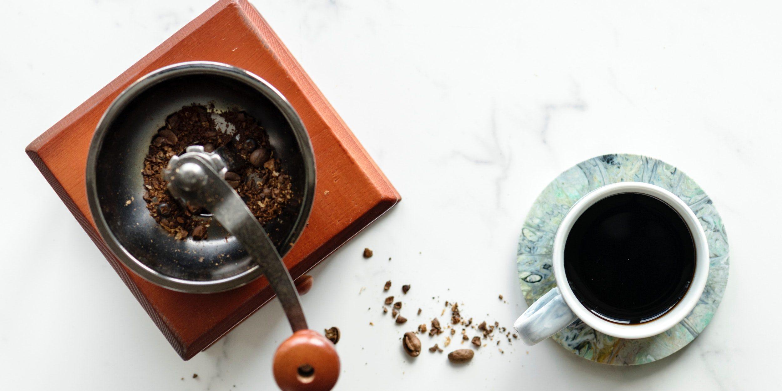 mesada de marmol con taza de café y molinillo de café